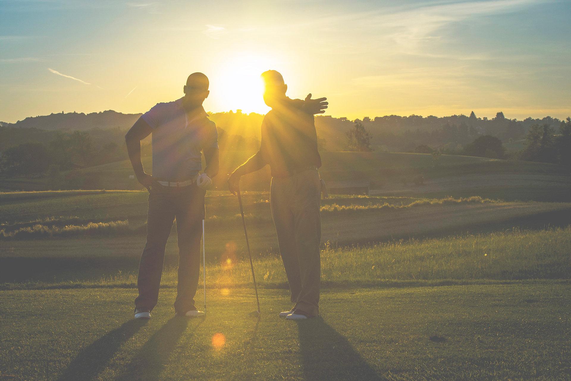 Golf pro teaching beginner golfer on driving range at sunset.
